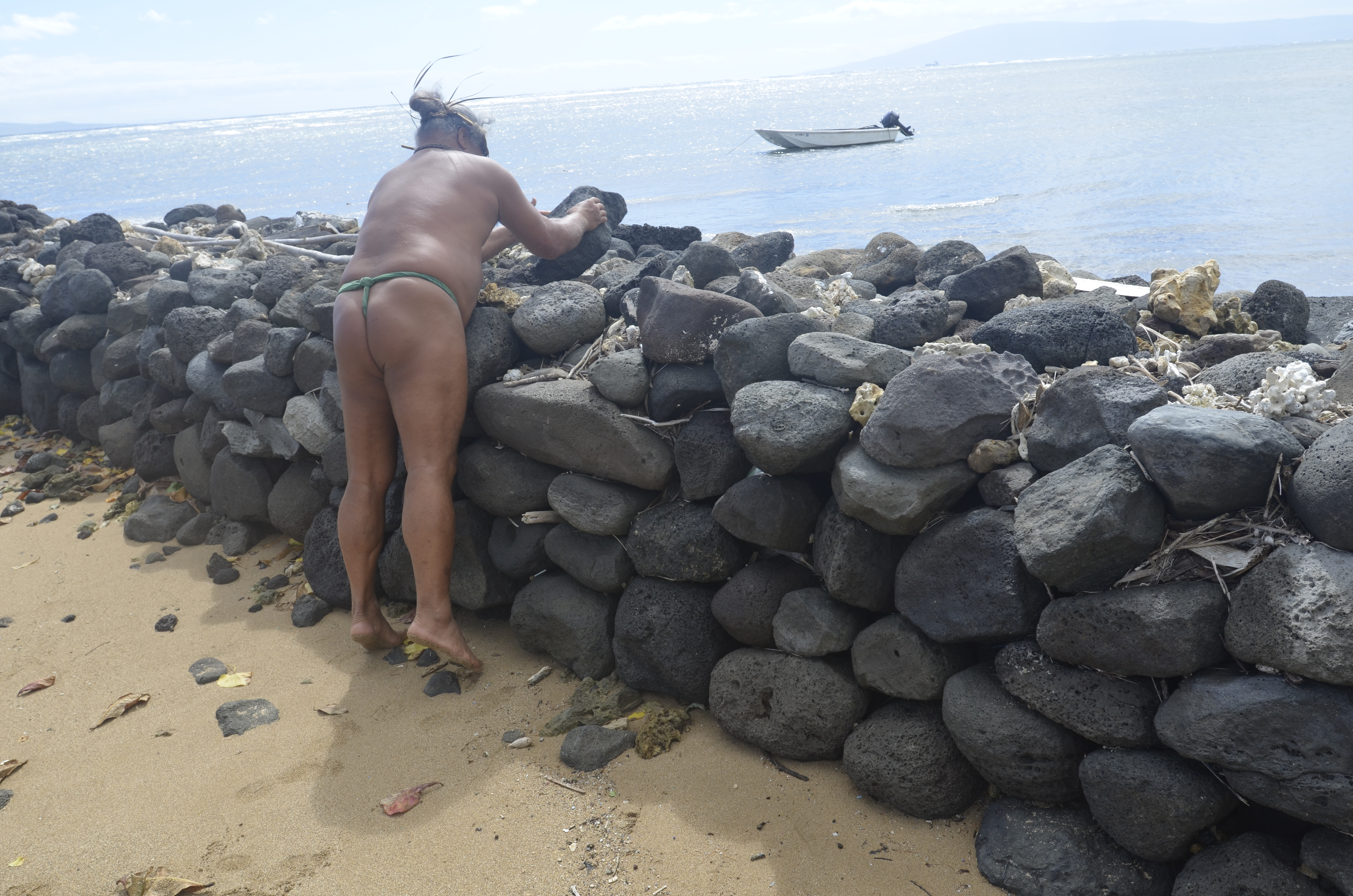 Leimana demonstrates the way to place rocks for a fishpond. He says hula builds up the right muscles for this.