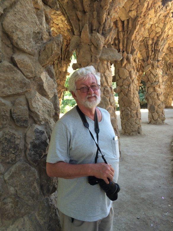 Tom standing under a Gaudi-designed bridge in Parc Guel