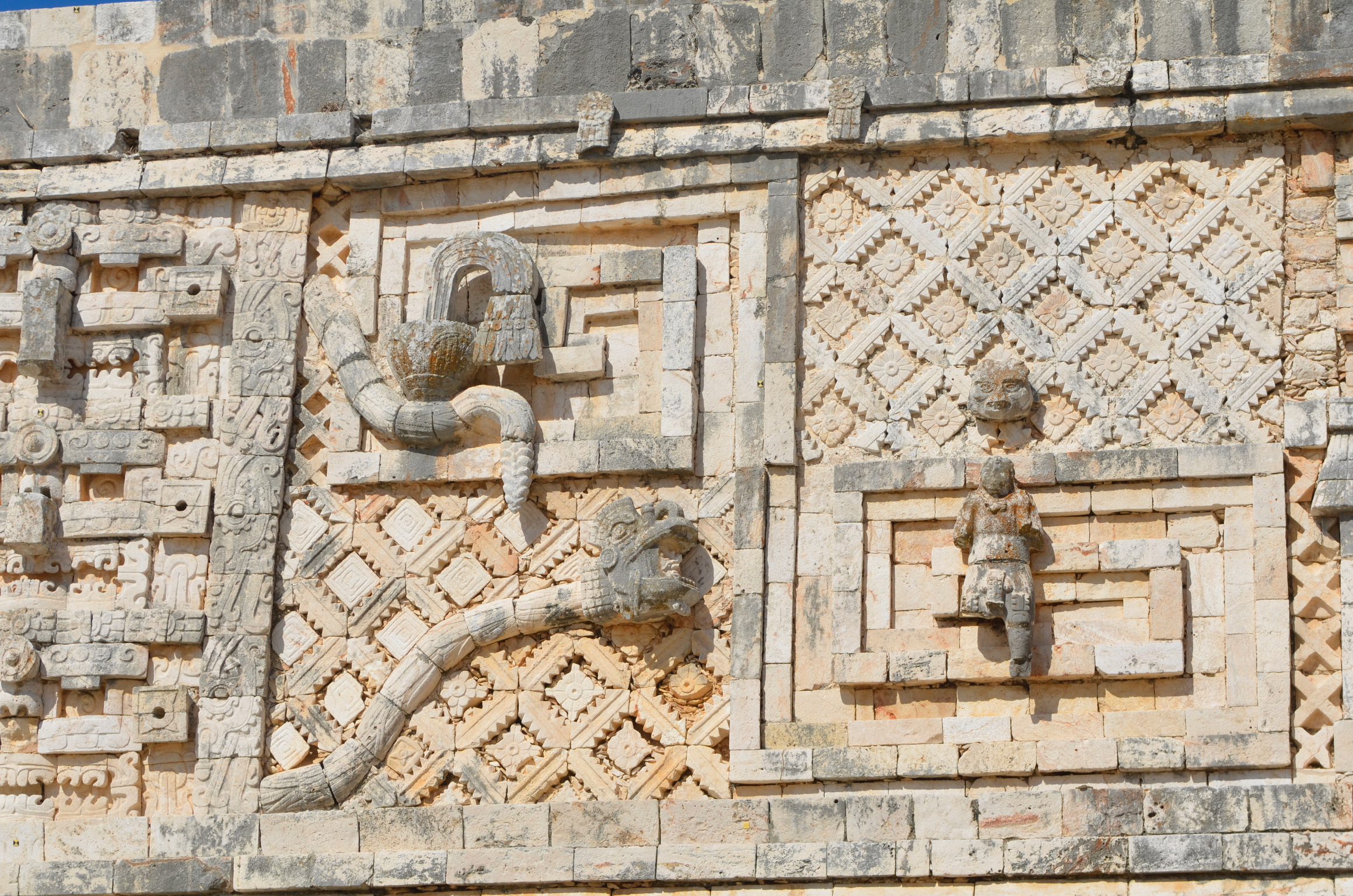 """The buildings at Uxmal are decorated with gorgeous bas-relief sculptures. You can see a plumed snake here, with a head emerging from its open mouth. This is the """"spirit snake"""" incarnation of Kulkulcan, enabling the spirit of an ancestor to communicate with the living."""