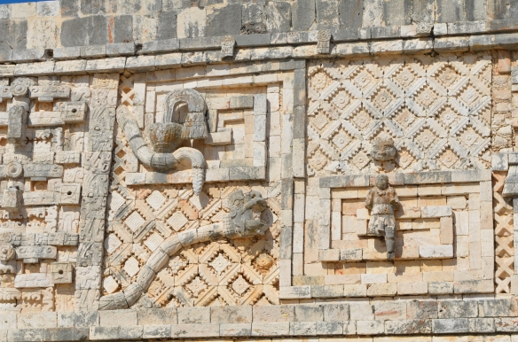 "The buildings at Uxmal are decorated with gorgeous bas-relief sculptures. You can see a plumed snake here, with a head emerging from its open mouth. This is the ""spirit snake"" incarnation of Kulkulcan, enabling the spirit of an ancestor to communicate with the living."
