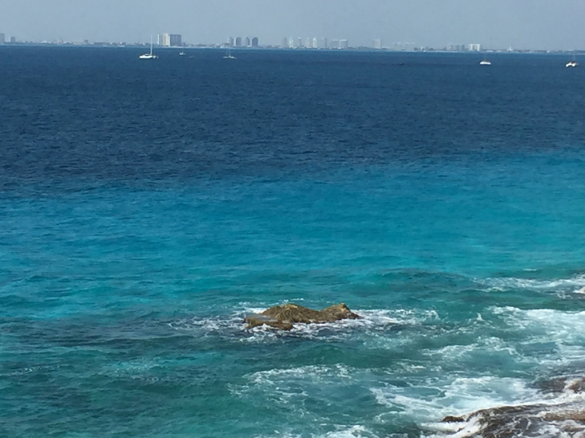 Cancun in the distance, across the blue, blue water.